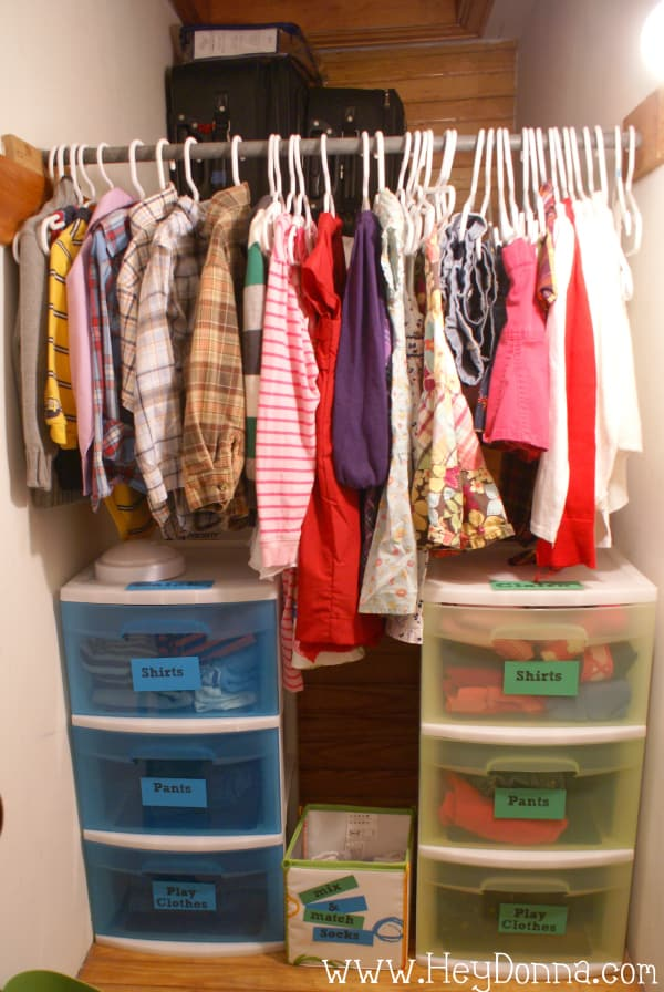 Organized hanging kids clothes. Children's clothes in drawers